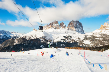 Skiers riding on the ski slope in winter Dolomites, Italy Wall mural