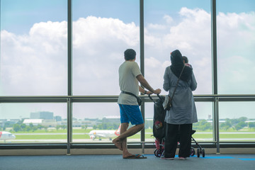 family looking aeroplant in airport during traveling in holiday