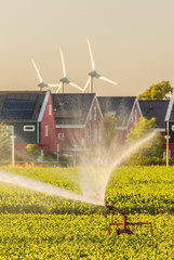 Irrigation sprinkler in front of Dutch houes with solar panels and windmills
