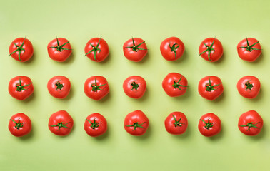 Creative pattern of red tomatos on green background. Top view. Copy space. Minimal design. Vegetarian, vegan, organic food and alkaline meal concept