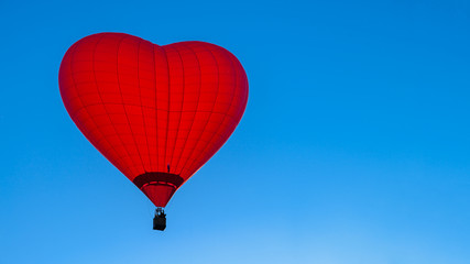 Photo sur Aluminium Montgolfière / Dirigeable Bright red hot air balloon in the shape of heart against blue sk