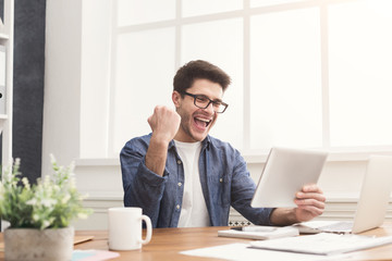 Young happy businessman in office with tablet