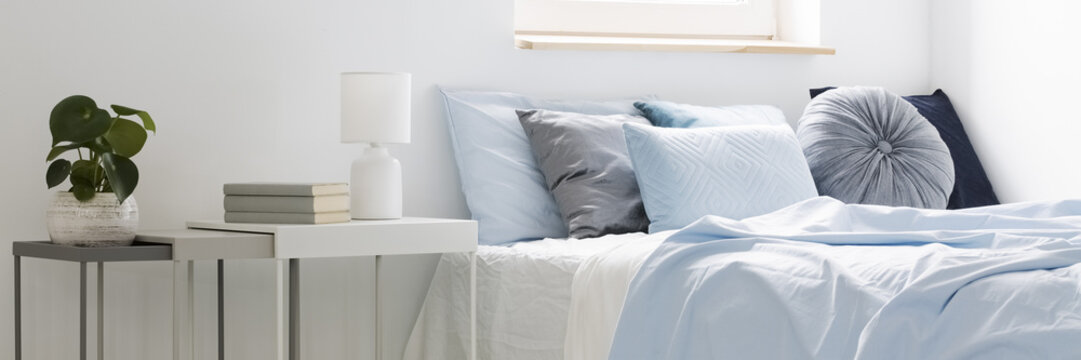 Real photo of a bed with blue bedding and cushions standing next to white tables with books, lamp and plant in bedroom interior