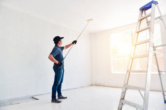 Asian rear view of a male painter drawing a wall with paint roller and a separate tank from a large empty space with wooden stairs.