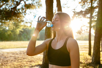 Side view of young sportive woman drinking a water from bottle after running in the park, outdoors. Dressed in sportswear.