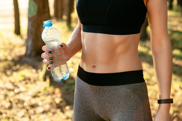 Close-up view of female body, woman holding a bottle of water, during workout in the park, wearing leggings and black tank top.