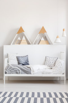 Triangles on white headboard above bed in teenager's bedroom interior with carpet. Real photo