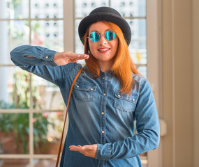Stylish redhead woman wearing bowler hat and sunglasses gesturing with hands showing big and large size sign, measure symbol. Smiling looking at the camera. Measuring concept.