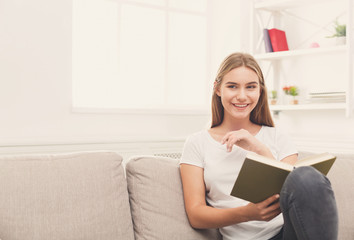 Cozy home. Young smiling woman with book