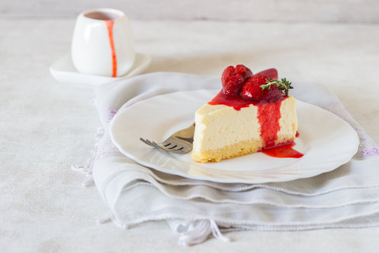 Piece of delicate cheesecake with strawberries sauce on a white plate.