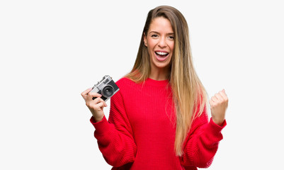 Beautiful young woman holding vintage camera screaming proud and celebrating victory and success very excited, cheering emotion