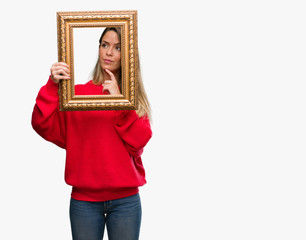 Beautiful young woman holding vintage frame serious face thinking about question, very confused idea
