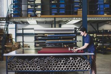 Male cutting fabric in a manufacturing warehouse