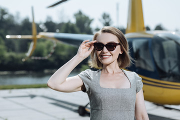 Ready for meeting. Pretty young woman adjusting her sunglasses and scanning the territory while waiting for the arrival of a helicopter pilot