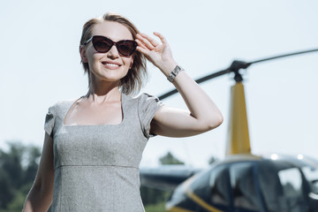 Satisfied with view. Upbeat young woman adjusting her sunglasses and smiling widely while standing at the heliport and scanning its territory
