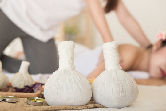 Herbals compress balls and blurred Young asian woman enjoying relaxing back massage in spa.  alternative medicine and relaxation Concept.