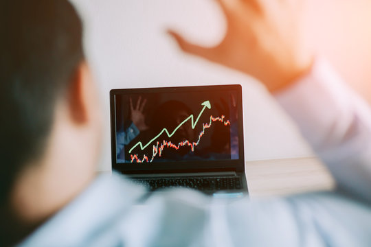 Business man look at to the laptop show financial market chart graphic going up. Bull market, Stock market concept.