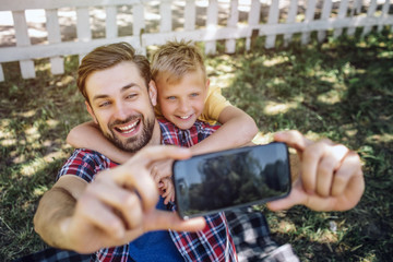 Adult and kid are looking on phone and smiling. Guy is holding device while child is hugging his dad. This picture is cute and awesome.