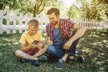 Small boy is sitting on grass with his dad with their legs crossed. Child is holding phone in hands and looking at it. He is smiling. Dad is looking at device too and smiling as well.
