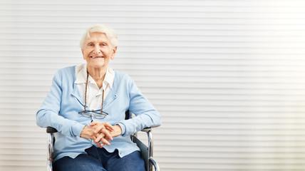 Alte Frau sitzt lächelnd im Rollstuhl im Seniorenheim