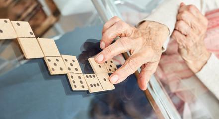 Hände von Senioren legen Spielsteine beim Domino