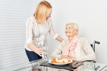 Pflegedienst Frau serviert alter Frau ein Essen