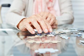 Hände von Senioren beim Puzzle spielen Wall mural