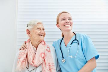 Lächelnde Pflegedienst Frau mit glücklicher Seniorin