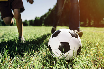 A picture of legs of two people playing football game. They are playing on green and juicy grass. It is sunny outside.