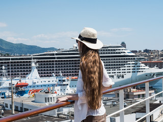 Beautiful, fashionable woman with long hair standing on the deck of a cruise ship against the background of a port with ships on a sunny, clear day. Concept of sea travel and recreation