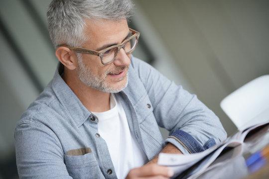 Middle-aged guy with trendy eyeglasses reading magazine