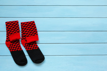 Pair of colorful socks  on a wooden background.