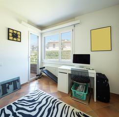 Studio with desk, computer, windows and balcony