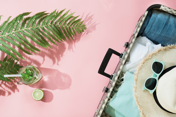 Leaf of fern, tropical detox water and open suitcase with clothes on pastel pink. Top view with copy space. Summer concept travel.