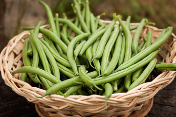 Green pods of fresh asparagus beans In a wooden wicker basket.