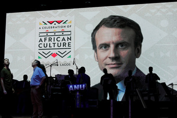 A photograph of France President Emmanuel Macron is projected on a screen as musicians rehearse on a stage, a day before his arrival, at the African shrine in Lagos