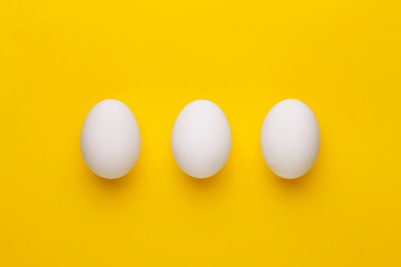 Three white eggs on a yellow background. Top view