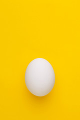 Single white chicken egg on a yellow background. Top view. Copy space
