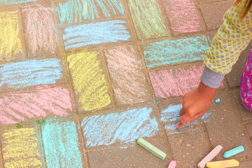 The child painted the asphalt with colored chalk.