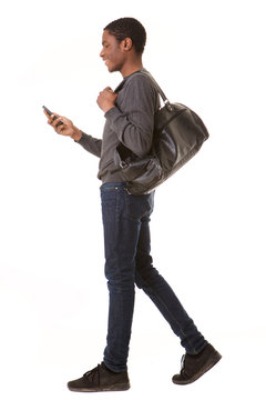 portrait of happy african american man walking with mobile phone and bag