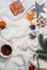 Hot cup of tea with tangerines and sweaters on bed background with lights. Cosy winter concept.