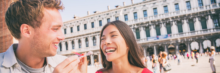Wall Mural - Happy multiracial couple eating gelato ice cream panorama banner. Smiling young people feeding each other with spoon laughing on San Marco Square in Venice, Italy, Asian girl, Caucasian man.