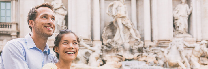 Wall Mural - Smiling couple of multiracial people at Trevi fountain in Rome, Italy. Europe summer travel elegant Asian woman with Caucasian man happy portrait banner panorama.