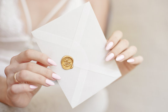 close-up woman with slim body holding invitation envelope card in hands, rear veaw.