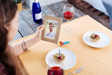 Husband on photo. Dark-haired woman looking at photo of her husband waiting for him for nice dinner