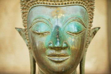 Close up of a face of an ancient copper Buddha statue outside of the Hor Phra Keo temple (former temple of the Emerald Buddha) in Vientiane, Laos.