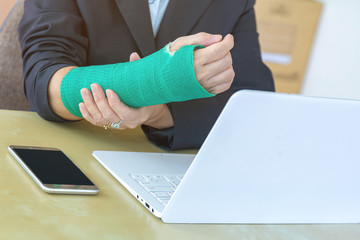 injured woman with broken hand sitting and holding green cast working with laptop in office