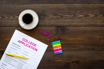 Apply college. Empty college application form near coffee cup and stationery on dark wooden background top view copy space