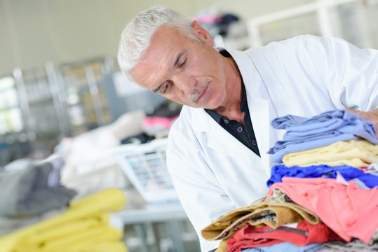 Man in laundry with pile of washing