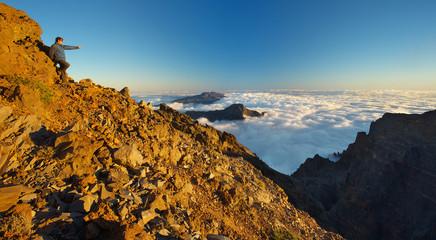 Resting man showing to a landscape above the crater Caldera de Taburiente, Island of La Palma, Canary Islands, Spain